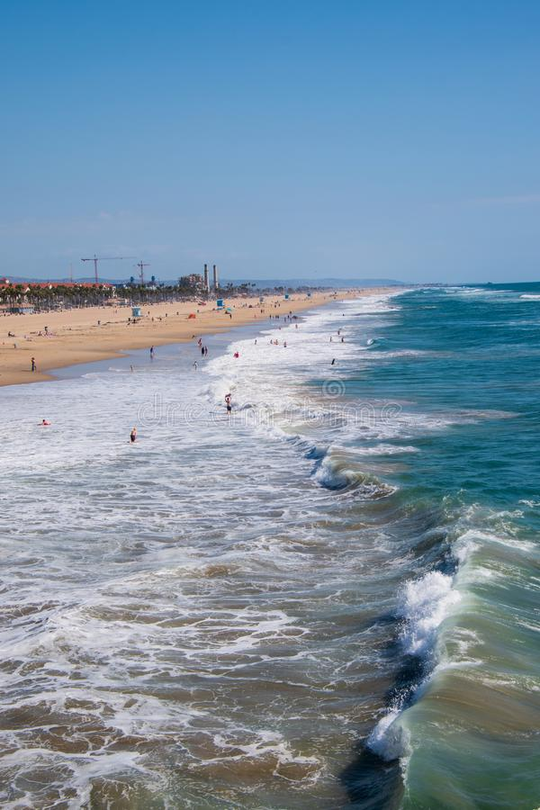 View up Huntington Beach with rough ocean with bathers and surfers. Drone view. Huntington Beach, California - October 11, 2018: View up the beach and rough royalty free stock photos