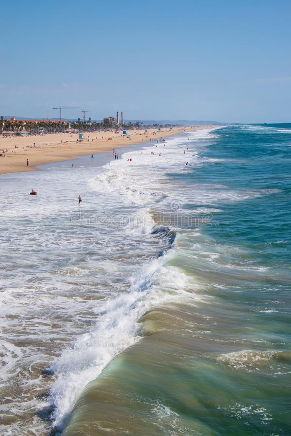 View up Huntington Beach with rough ocean with bathers and surfers. Drone view. Huntington Beach, California - October 11, 2018: View up the beach and rough stock image