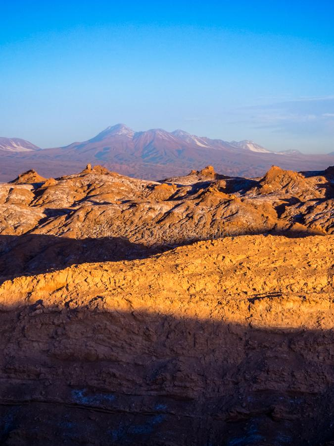 View of the Valley of the Moon in San Pedro de Atacama at sunset. In the background the volcano Licancabur and the Juriques royalty free stock image