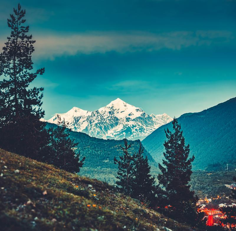 View from the valley to the Caucasus Mountains. Majestic view from the green valley to the mighty snow-capped Caucasus Mountains in Georgia. Gorgeous serene stock photo