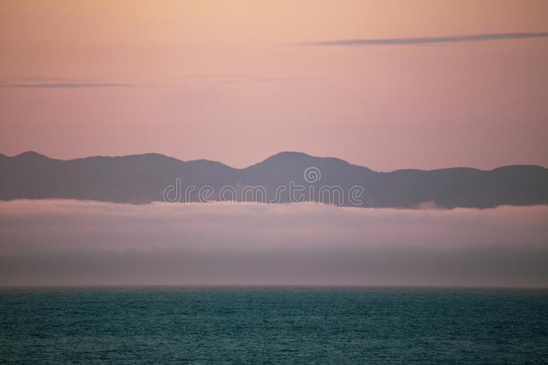 View of Vancouver Island from Port Angeles: the famous Washington State mist on the sea, with mountains in the background. Soft,. Romantic scenery royalty free stock photo