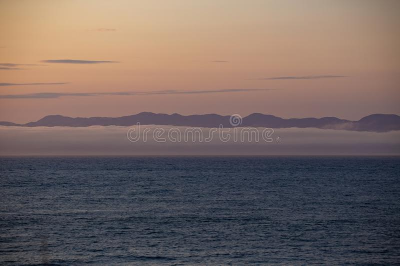 View of Vancouver Island from Port Angeles: the famous Washington State mist on the sea, with mountains in the background. Soft,. Romantic scenery stock photography