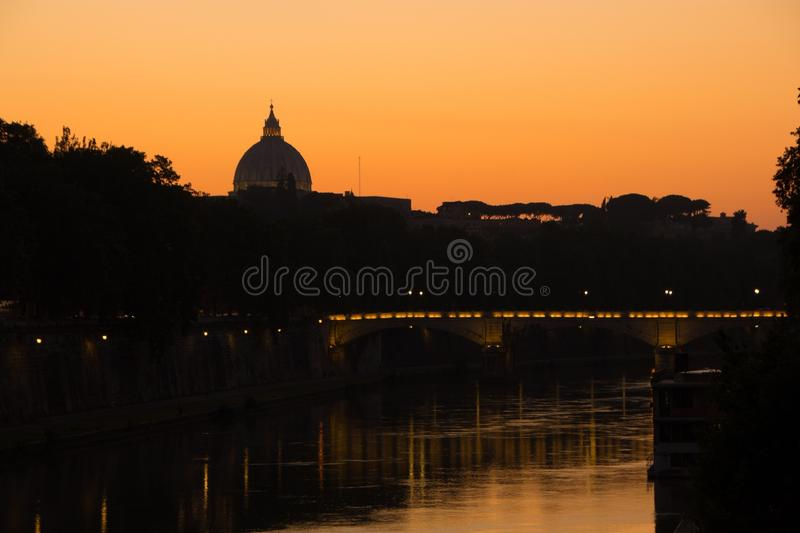 Rome, Italy - May 31, 2018: View of the Vatican dome across the Tiber river and the bridge. Colorful sunset and lighting. royalty free stock photo
