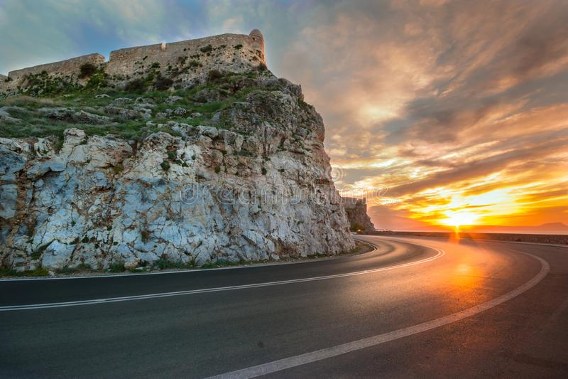 View of the Venetian castle on top of the hill, with perspective road at sunset Rethymno, Crete. royalty free stock photos