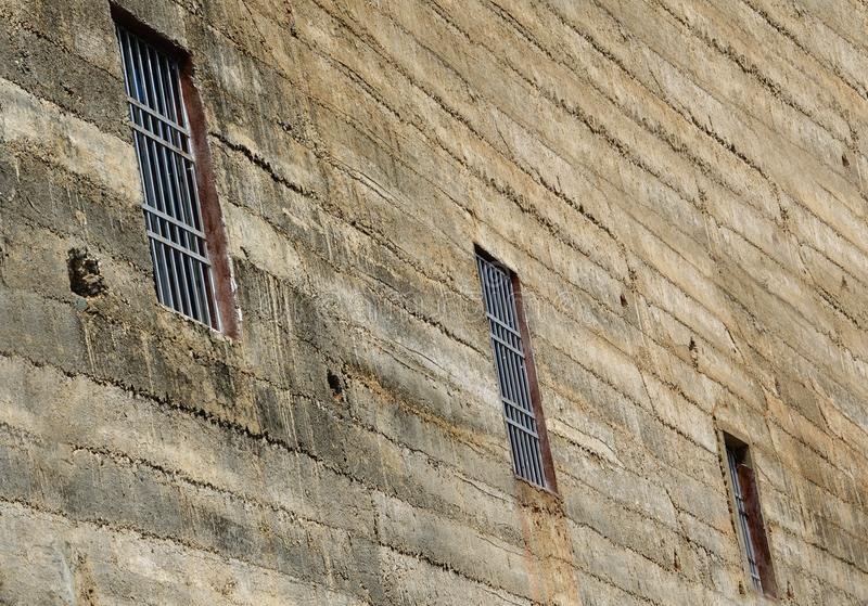 View of a very rustic wall with barred windows stock photography