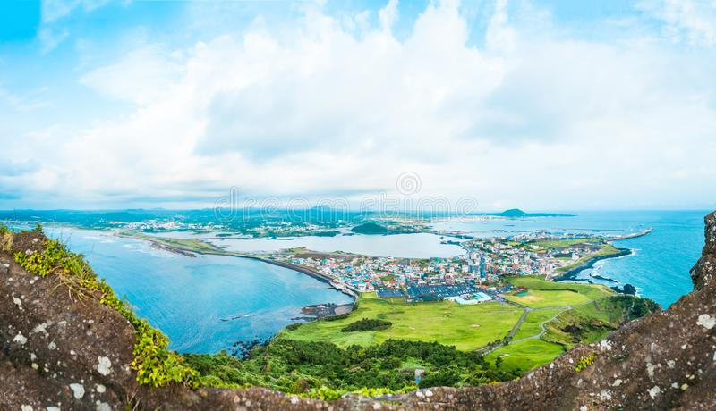 View from the very top of famous Seongsan mountain on a windy day at the shore of Jeju Island - South Korea royalty free stock photo