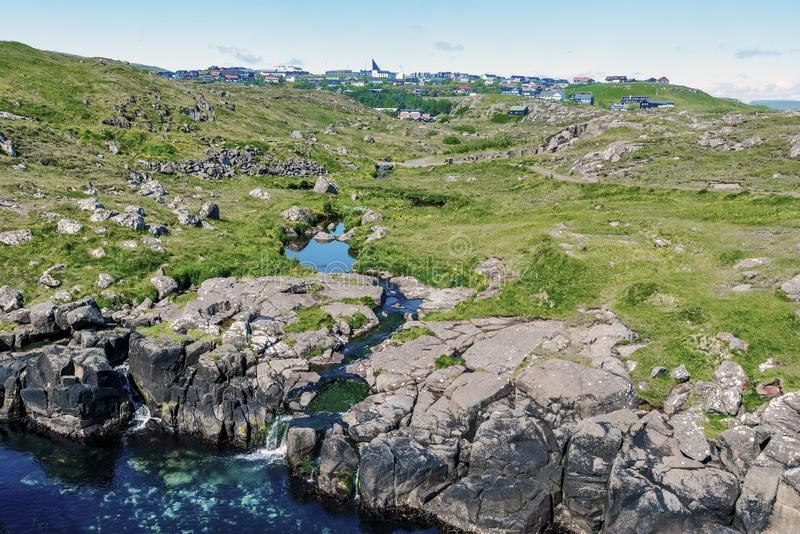 View via Hoyvik agglomeration from Hoydalsa river course. Joining ocean waters in Faroese island of Streymoy royalty free stock image