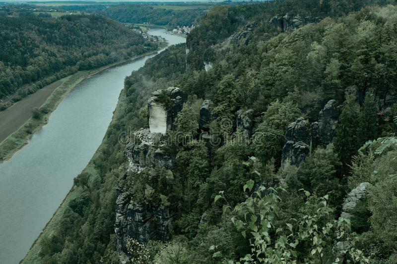View from viewpoint of Bastei in Saxon Switzerland Germany to the town city and the river Elbe. Misty landscape with fir forest. In hipster vintage retro style stock images