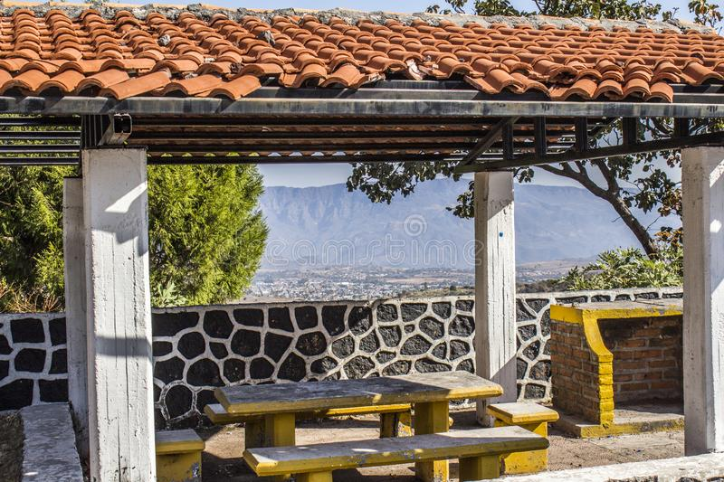 View of a viewpoint with a tile roof. Concrete benches and table with the town of Tequila Jalisco Mexico background royalty free stock photography