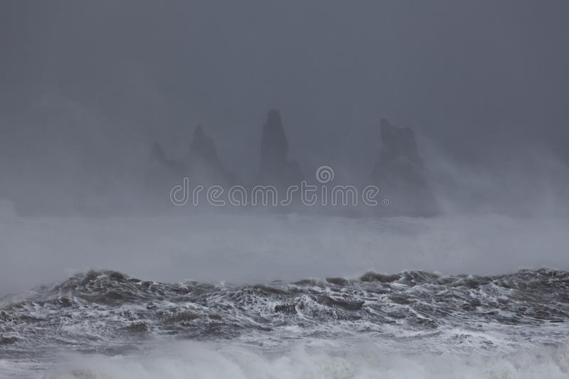 View from Vik beach during heavy storm, Iceland. Splashing waves in the foreground. Storm on Atlantic ocean. Breathtaking morning view of Reynisdrangar cliffs stock photography
