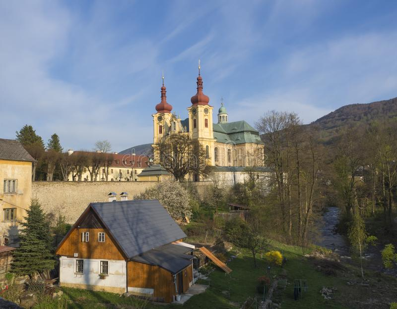 View on Village Hejnice with cottages, creek and Baroque Basilica church of the Visitation Virgin Mary in spring, golden. Hour light, place of pilgrimage stock photos