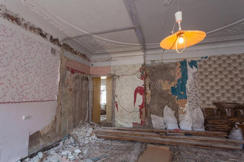 View the vintage room with fretwork on the ceiling of the apartment during under renovation, remodeling and construction. Garbage of constraction materials and stock photo