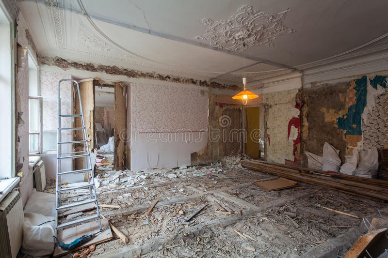 View the vintage room with fretwork on the ceiling of the apartment during under renovation, remodeling and construction. Ladder, garbage of constraction stock photo