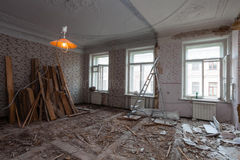 View the vintage room with fretwork on the ceiling of the apartment during under renovation, remodeling and construction. Ladder, garbage of construction stock photography