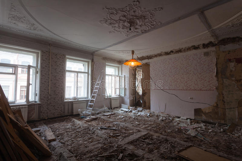 View the vintage room with fretwork on the ceiling of the apartment during under renovation, remodeling and construction. Ladder, garbage of constraction royalty free stock photos