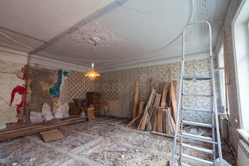 View the vintage room with fretwork on the ceiling of the apartment during under renovation, remodeling and construction. Ladder, garbage of contraction stock photo