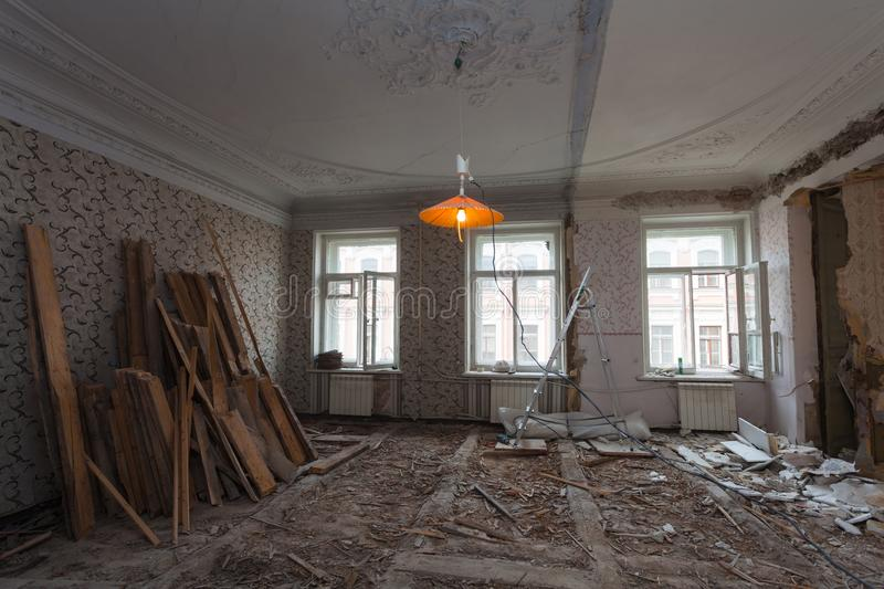 View the vintage room with fretwork on the ceiling of the apartment during under renovation, remodeling and construction. Ladder, garbage of constraction stock photos