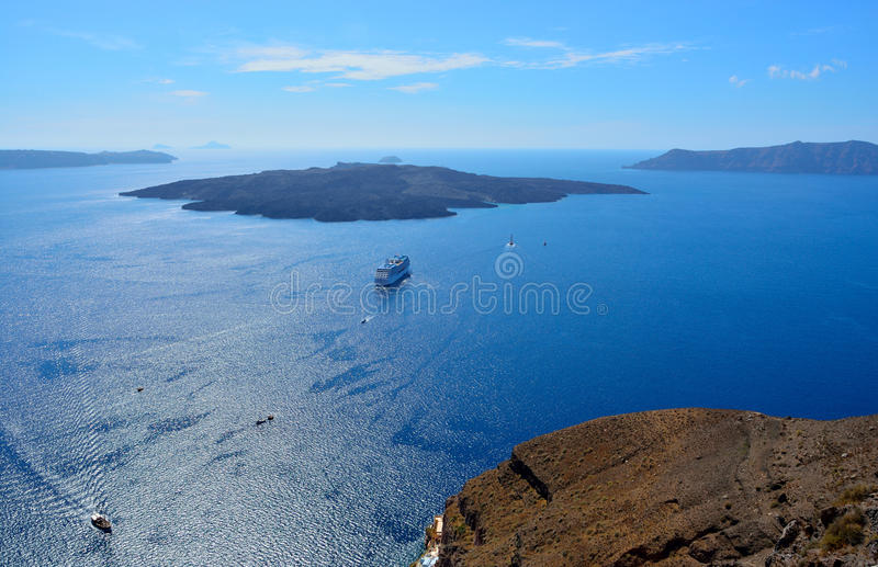 View of the volcano in the Aegean Sea near the island of Santorini. The sunlit sea, sailing ships, the volcano, the island of Santorini, Greece stock images