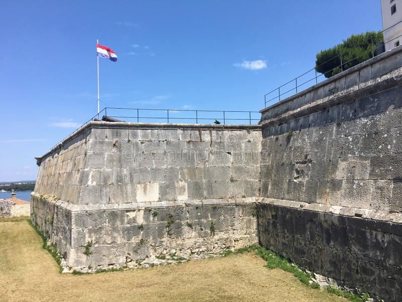 A view of the walls of Pula Castle, a venetian fortress and popular tourist site.  The croatian flag flaps in the wind. stock images