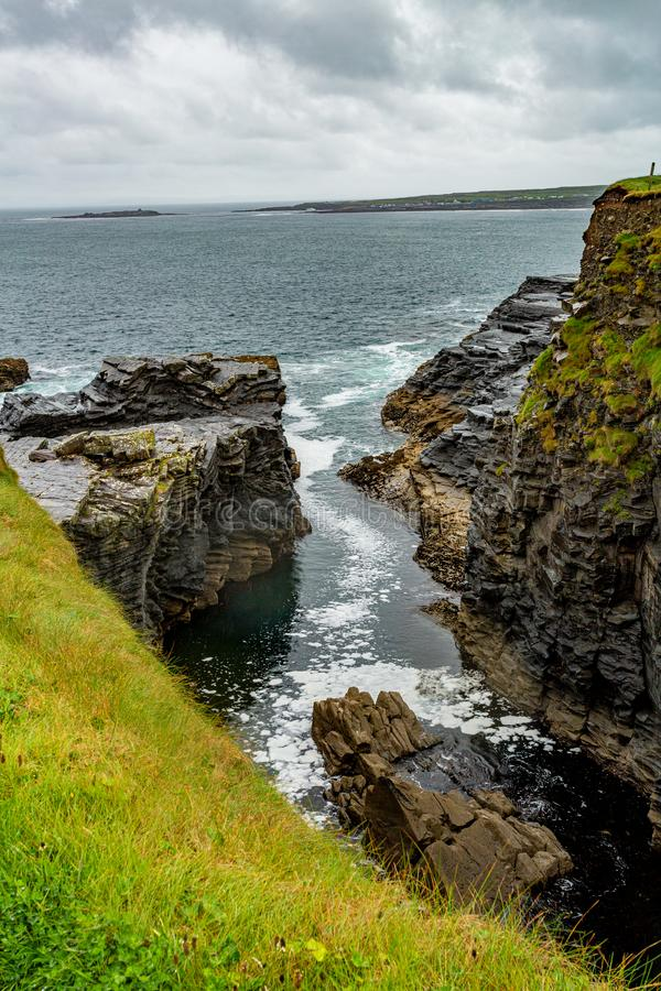 View of the water inlet on a rocky cliff in the coastal walk route from Doolin to the Cliffs of Moher. Geosites and geopark, Wild Atlantic Way, rainy day in royalty free stock photography