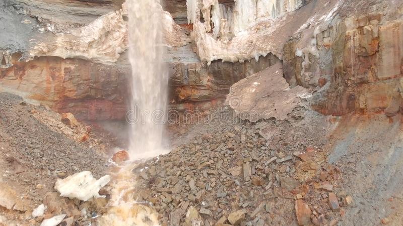 View of waterfall on background of dirty mineral rock. Stock. Dirty waterfall trickle down mineralogical brown rock wall royalty free stock photography