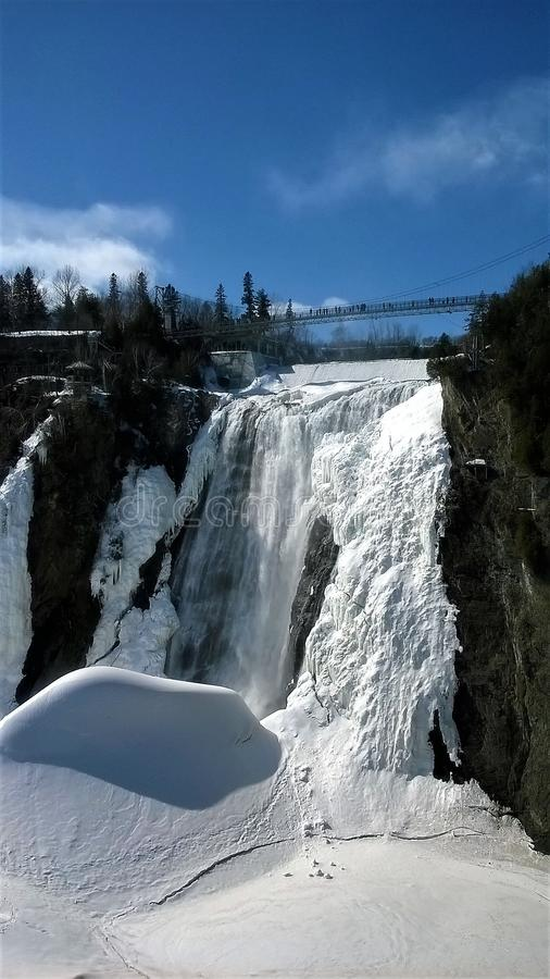 View of a waterfall under a beautiful winter day in Quebec Canada. View of a waterfall under a beautiful blue sky on a winter day in Quebec Canada. Montmorency royalty free stock photos