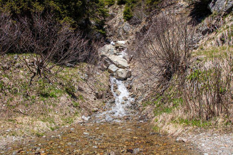 View of waterfalls and mountain streams with a lot of melt water. In spring in the swiss alps royalty free stock image