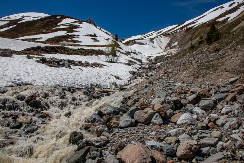 View of waterfalls and mountain streams with a lot of melt water. In spring in the swiss alps royalty free stock photos
