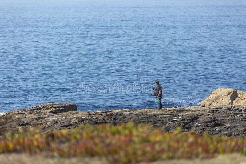 View at the waters sea and cliff of rocks, with a fisherman and fishing rods, on the coast royalty free stock photo