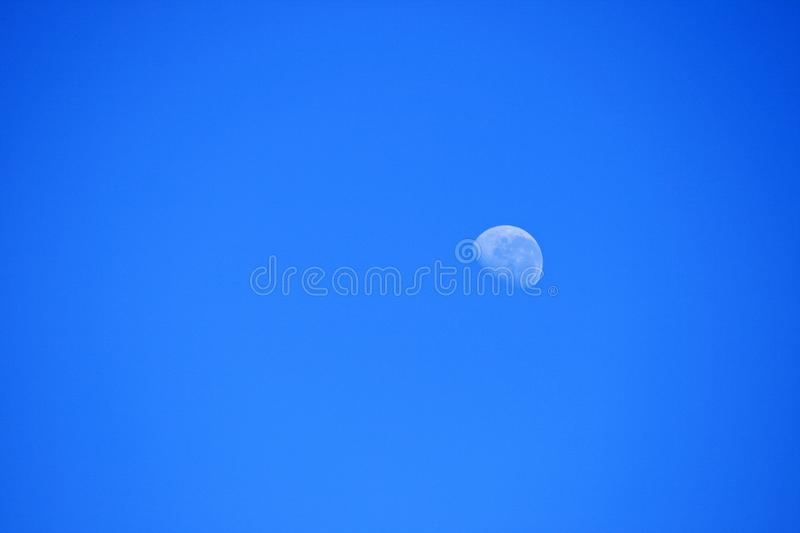 VIEW OF WAXING MOON IN MORNING SKY royalty free stock image