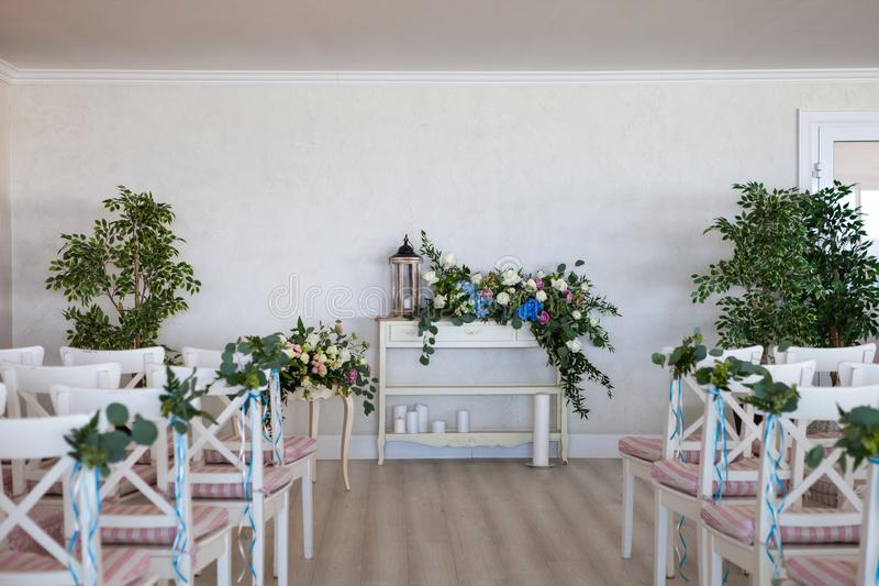 View of a wedding ceremony scene in a room with several rows of white chairs and compositions from different flowers stock photos