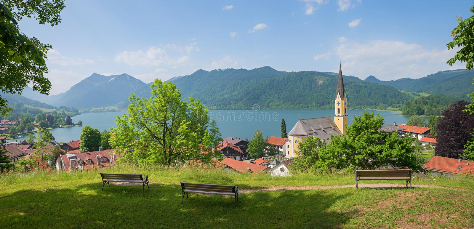 View from weinberg hill to spa town schliersee, st sixtus church. upper bavaria in summer. Three benches for rest at the hill top stock image