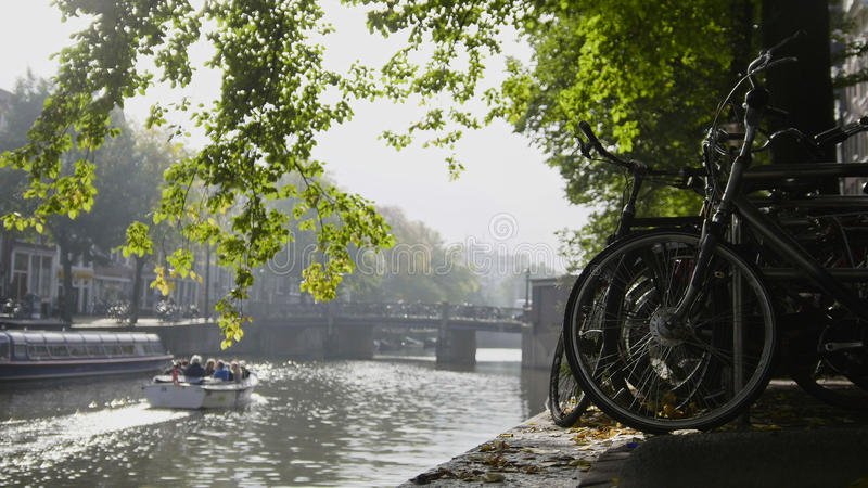 View of wheel bicycle on the Amsterdam amstel canal, next to floats tour boat, sunny european autumn. View of wheel of bicycle on the Amsterdam amstel canal stock photo