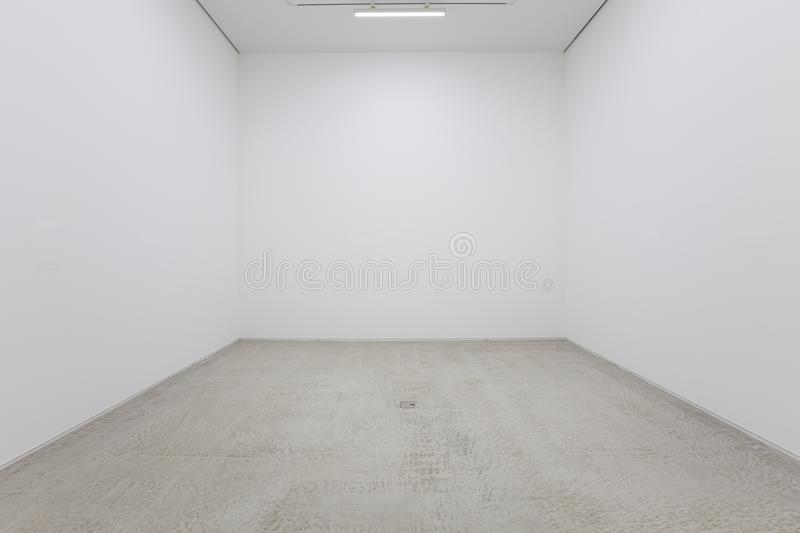 A view of a white painted interior of an empty room or an art gallery with a fluorescent lighting and wood floors royalty free stock image