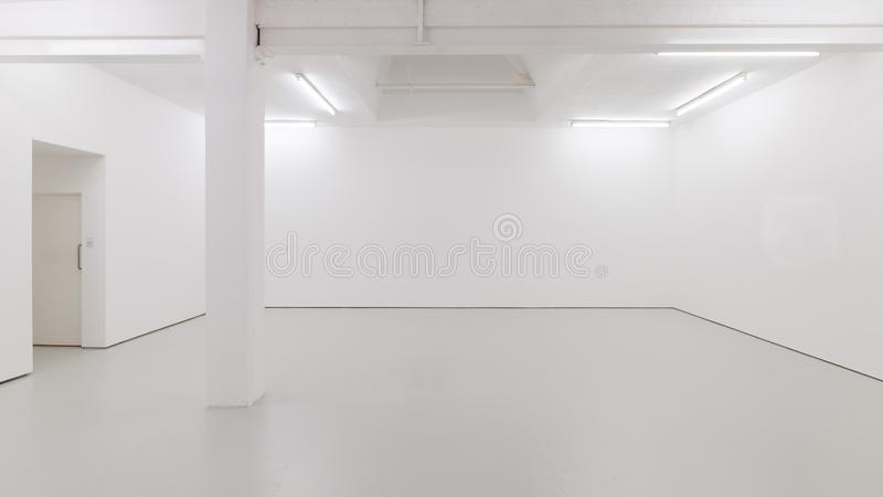 A view of a white painted interior of an empty room or an art gallery with a skylight lighting and concrete floors stock image