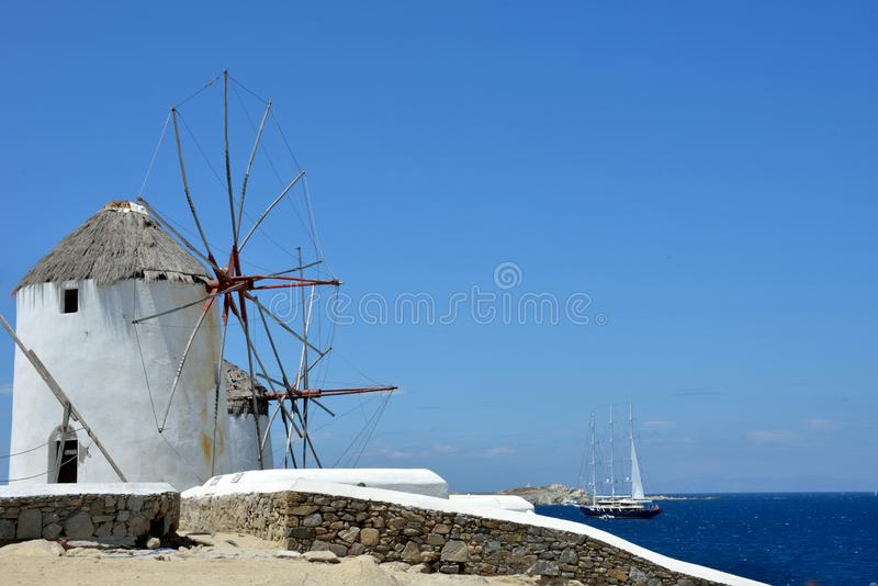 View of white windmill of Mykonos with a luxury sailboat sailing in the blue sea stock photo
