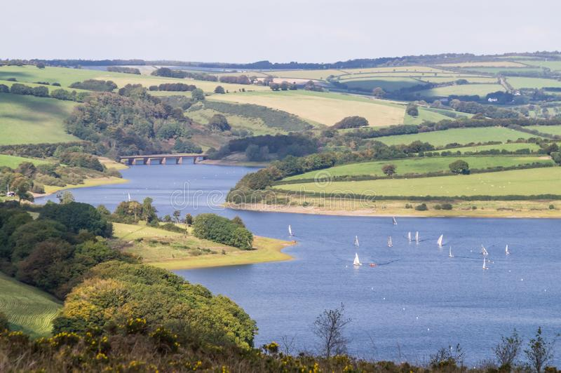 The view of Wimbleball Lake from Haddon Hill. With gorse bushes in the foreground , boats sailing on the lake in the middle distance and rolling countryside in royalty free stock photography