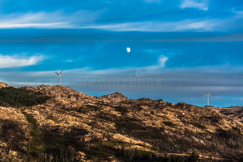 View of a wind turbines on top of mountains, dramatic sunset sky with a moon as background royalty free stock photography