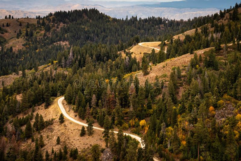 A view of a winding mountain road during the fall season stock photo