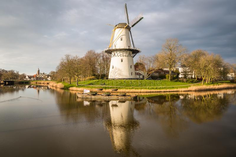 A view of a windmill at sunset on a canal just outside Middelburg, the Netherlands. A windmill on a canal at sunset on a spring day in Middelburg, the royalty free stock photo