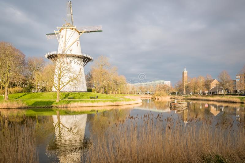 A view of a windmill at sunset on a canal just outside Middelburg, the Netherlands. A windmill on a canal at sunset on a spring day in Middelburg, the royalty free stock photography