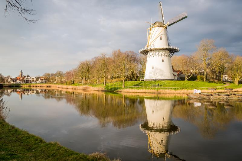 A view of a windmill at sunset on a canal just outside Middelburg, the Netherlands. A windmill on a canal at sunset on a spring day in Middelburg, the stock photography
