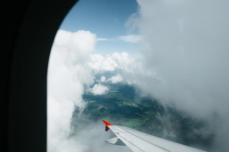 View from window flight on air with flight wing with beautiful blue sky and cloud. Beautiful scenic city view of sunset through the aircraft window. Image save stock images