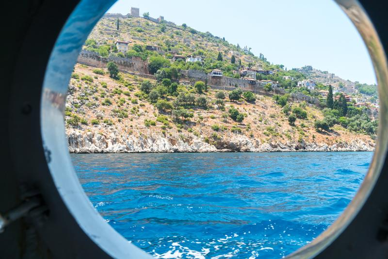 The view from the window of a marine vessel on the stone walls of the old coastal fortress of Alanya. View of sparse mountain vegetation and a small dwelling stock photos