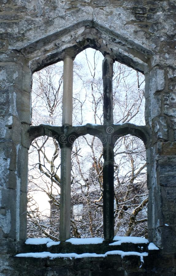 View through a window of a medieval ruined church in heptonstall yorkshire with snow covered trees behind the stone frame. A view through a window of a medieval royalty free stock photography