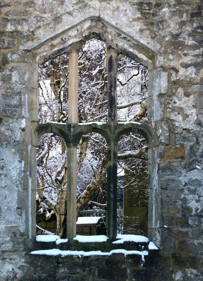 View through a window of a medieval ruined church in heptonstall yorkshire with snow covered trees behind the stone frame. A view through a window of a medieval stock photography