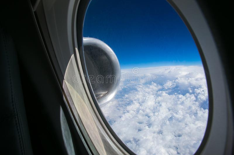 View from the window of the plane onto the wing and engines of a fokker 100 model with a blue sky and white clouds. Sunny weather stock photos