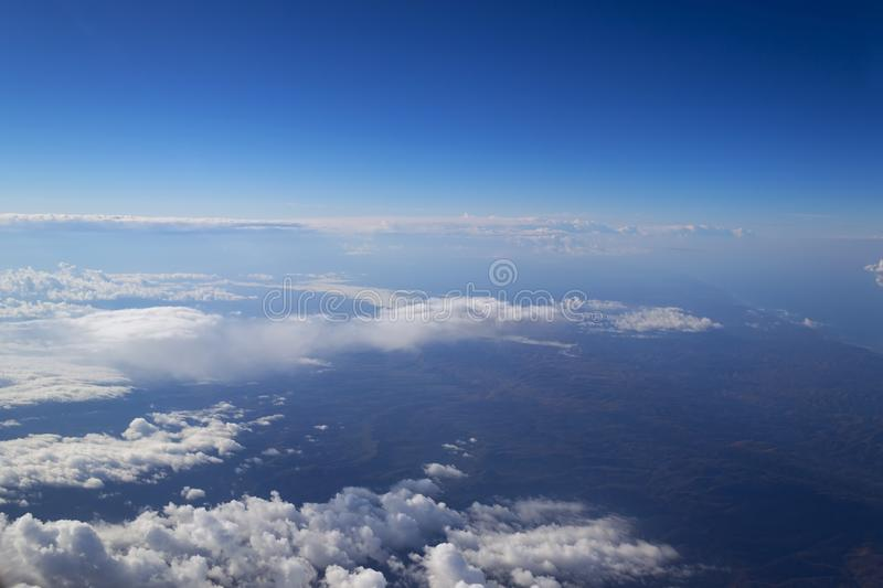 View from the window of the plane to the cumulus clouds and the infinitely blue sky. royalty free stock photos