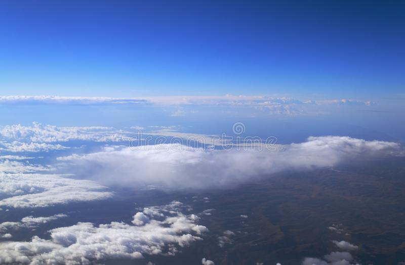 View from the window of the plane to the cumulus clouds and the infinitely blue sky. stock images