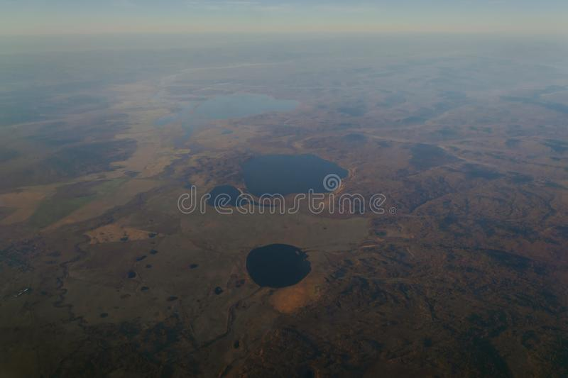 View from the window of the plane to the horizon of the lake and the river in the mountains with forests at sunset of the day stock images